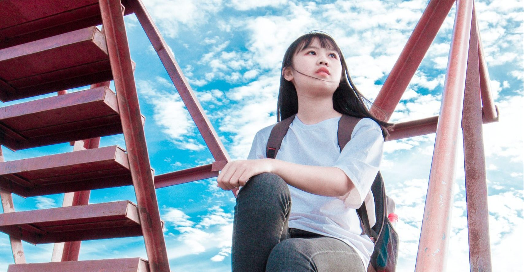 Photo of an Asian teen sitting on a playground ladder looking anxious representing what a teen might look like before receiving online anxiety treatment for kids in Illinois.