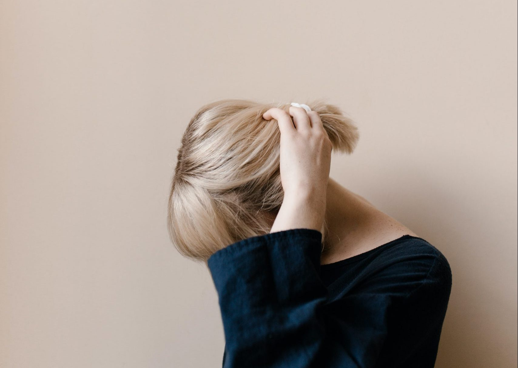 Photo of blond female teen with her head down and her left hand reaching for her ponytail thereby obscuring her face. This photo represents a teen with social anxiety who could use some online therapy in Illinois for social anxiety disorder.
