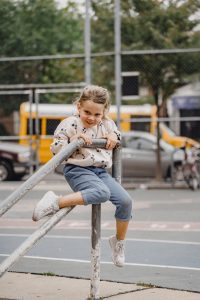 Photo of a smiling little cauasian girl playing on the steps of a city playground representing the results of online anxiety treatment in Illinois using solution focused brief therapy.