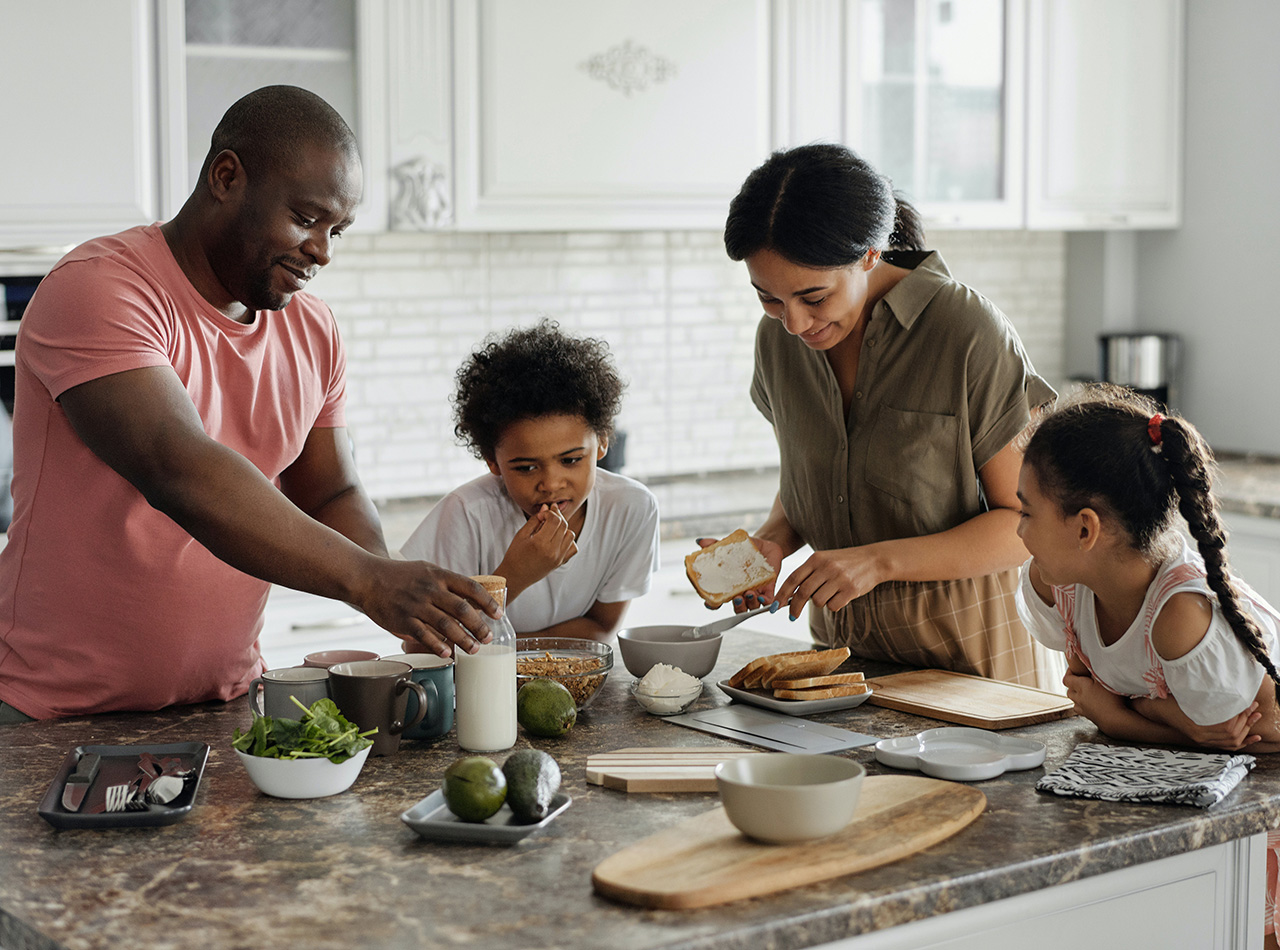 Photo of African American family smiling while making sandwiches together in the kitchm representing how helpful family counselign for anxiety in Illinois during Covid-19 was.