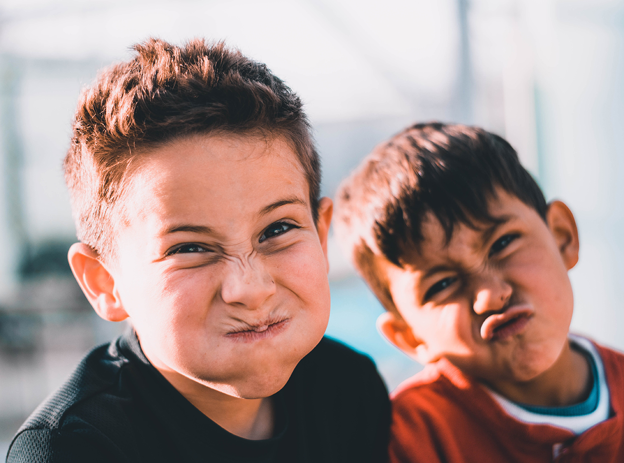 Photo of two young boys making silling faces representing their difficulty paying attention and their need for mindfulness training from an online therapist in Illinois.