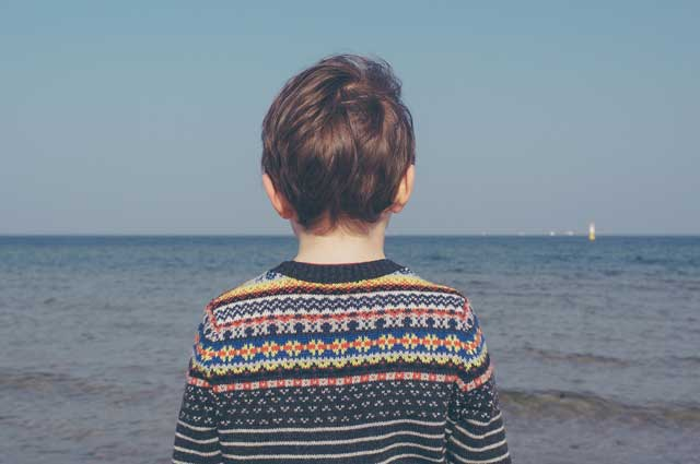 Photo of the back of a Caucasian's boy head as he stares ahead to the ocean in front of him. Photo represents his sadness and fear over his parent's upcoming divorce prompting his parents to reach out for online anxiety counseling for kids in Illinois.