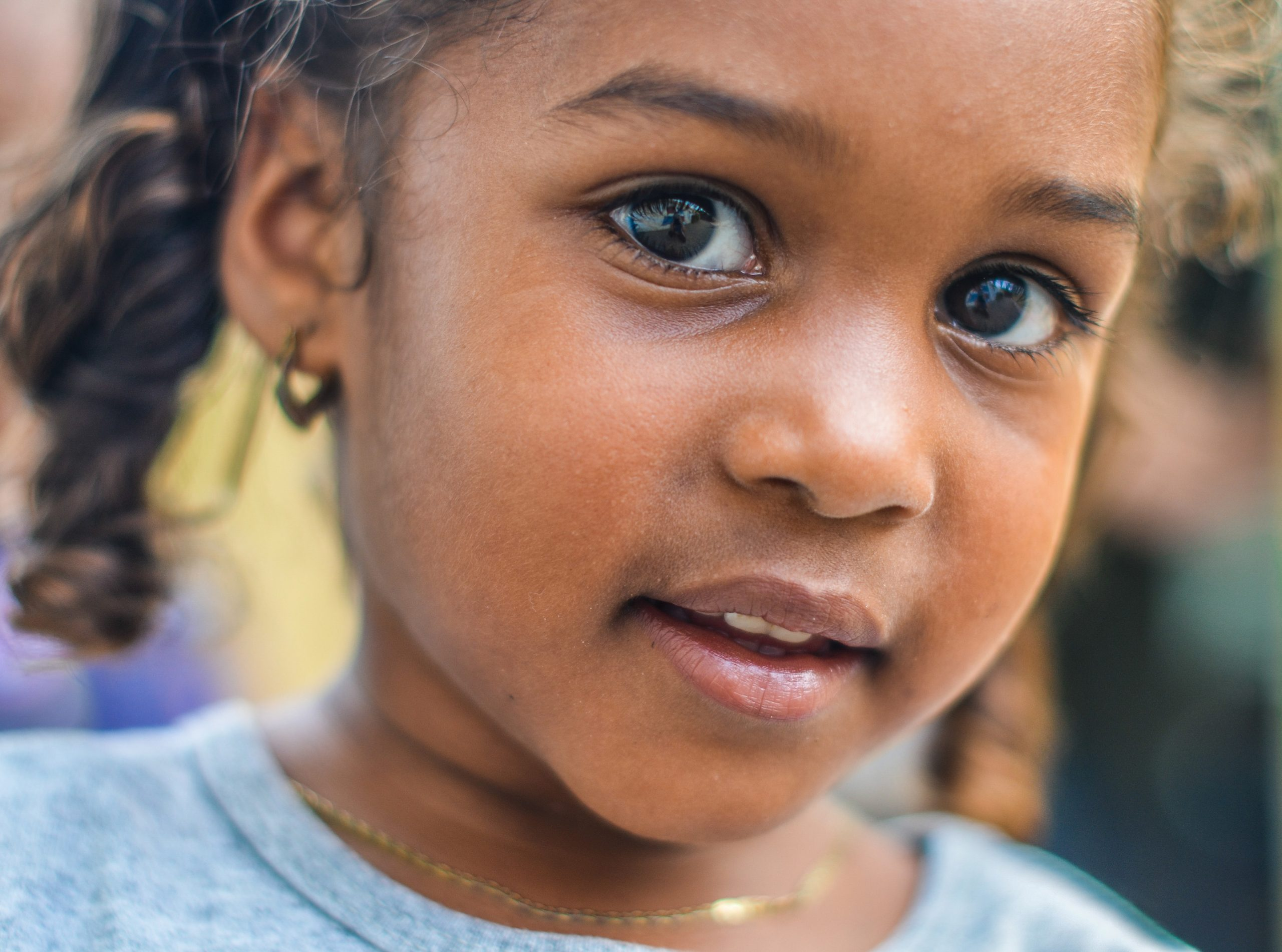 Close up photo of a young African American girl with a curious look on her face which could represent how she is learning resilience and confidence through her online anxiety treatment in Illinois.
