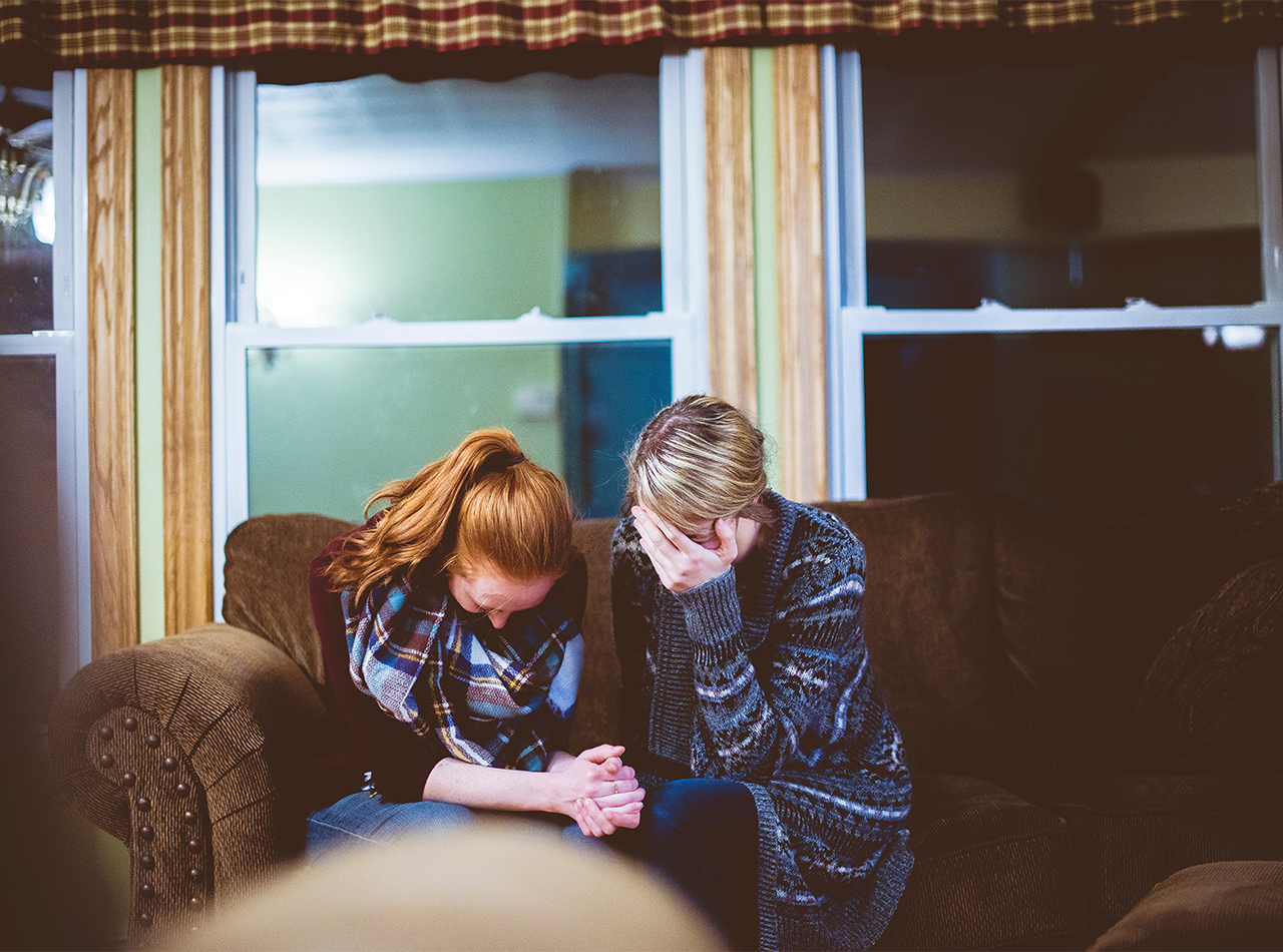 Photo of mom and teen daughter sitting on a brown sofa in the living room with their hands clasped in prayer and mom with one hand covering her face which could represent the grief they are experiencing from a recent death in the family and the need for online therapy in Illinois for grief and anxiety.