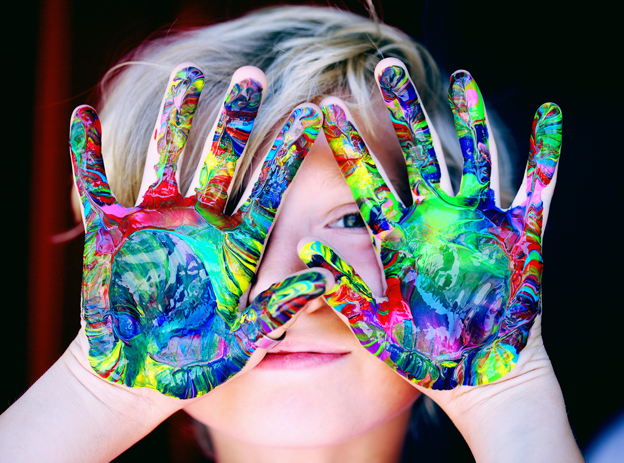 Photo of a young Caucasian boy holding up his finger painted hands in front of his face representing the ability to be creative in spite of his learning disabilities and how much better he feels since receiving counseling for kids with anxiety.