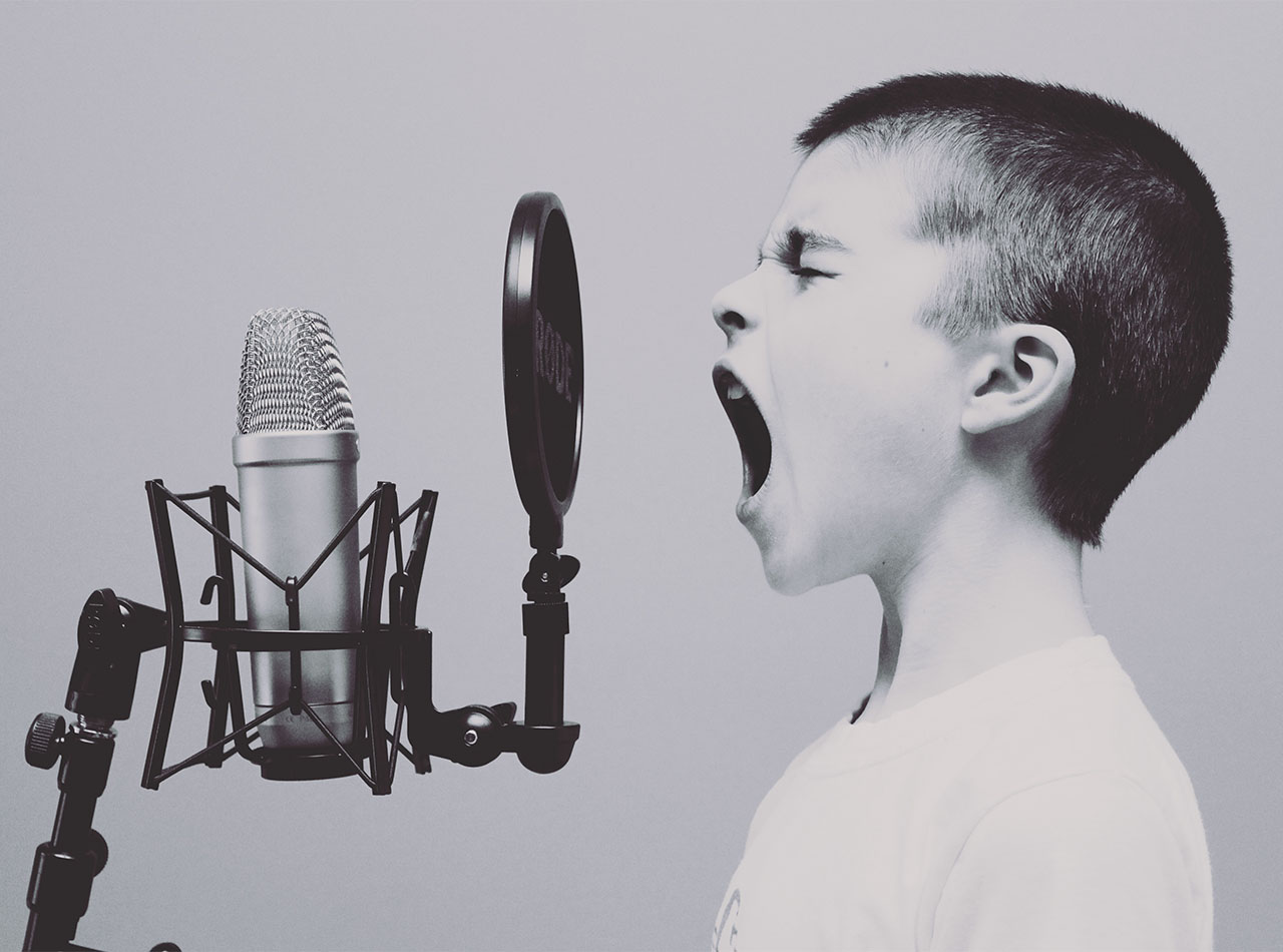 Black and white photo of a young Caucasian boy wearing a white t-shirt and yelling into an old fashioned microphone. Photo could represent how difficult it is for this boy to control his anger and his need for counseling from an online therapist in Illinois.