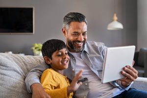 Father on couch with son while beginning online therapy for kids. Kids are a great gift, but when they are suffering, we are all affected. Therapy for children in Illinois can help. You child can reduce stress and anxiety. Plus become more confident in therapy. Begin with Briefly counseling for online therapy in Illinois today!