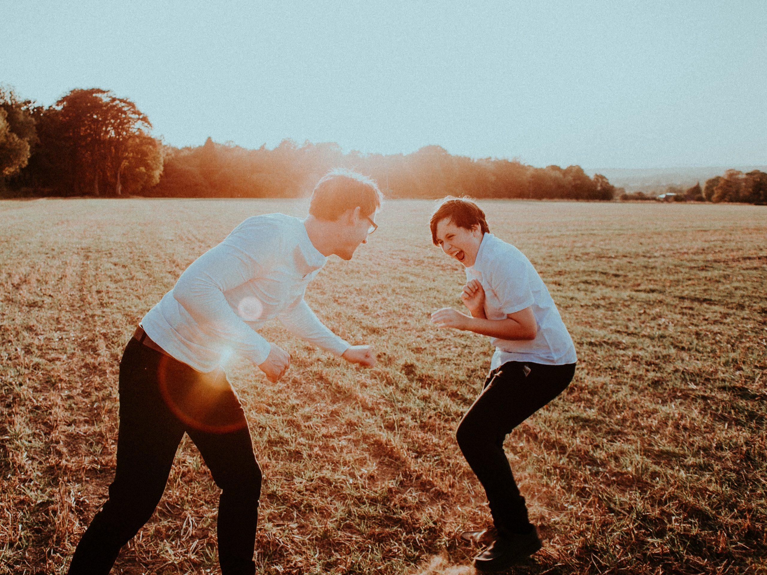 Photo of laughing Caucasian father and teenaged son playing around in an open grassy field representing one of one time spent together on the recommendation of their online anxiety therapist for teens in Illinois.