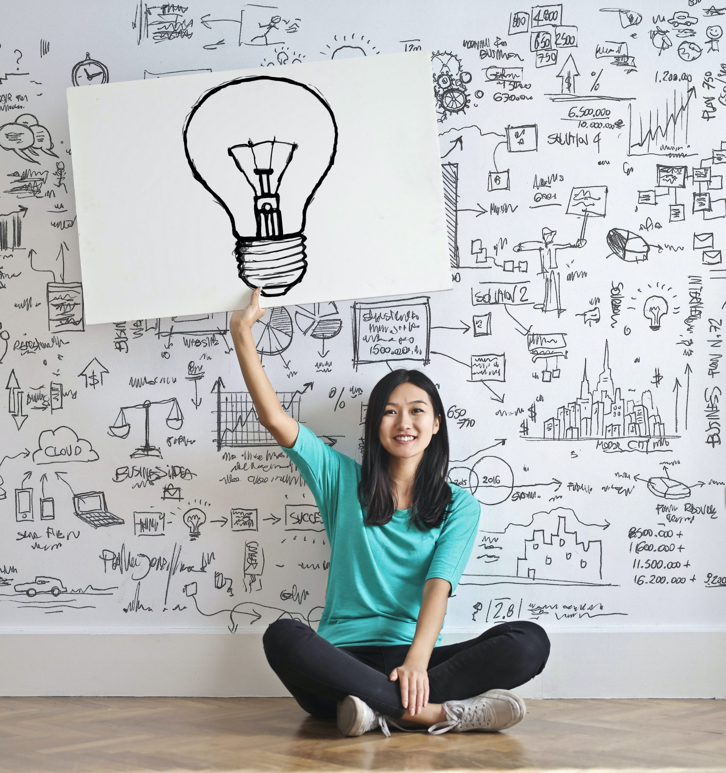 Young asian teen holding up sign with drawn on light bulb in front of why wall with drawings. Anxiety solutions don't need to take months. Solution-focused therapy in Illinois can help. Begin online therapy with a solution-focused therapist soon and see your children thrive.