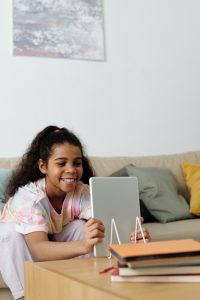 Photo of African American girl smiling while leaning forward on her elbows with her laptop in her hands. Its time to help your child overcome their distress. Try working with a skilled online anxiety therapist in IL who can help. Begin therapy for anxiety in kids in Illinois today!