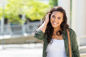 Happy latina teen smiling and brush hair back with hand. Learn to overcome anxiety. Your teen can find faster solutions working with a solution-focused therapist. Begin solution-focused brief therapy today!