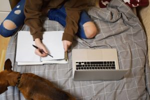 Young teen in brown sweater taking notes while on laptop. Your teens may have questions about online anxiety counseling for teens in Illinois. Learn more about online therapy through my FAQs about counseling. Begin online counseling for teens soon!