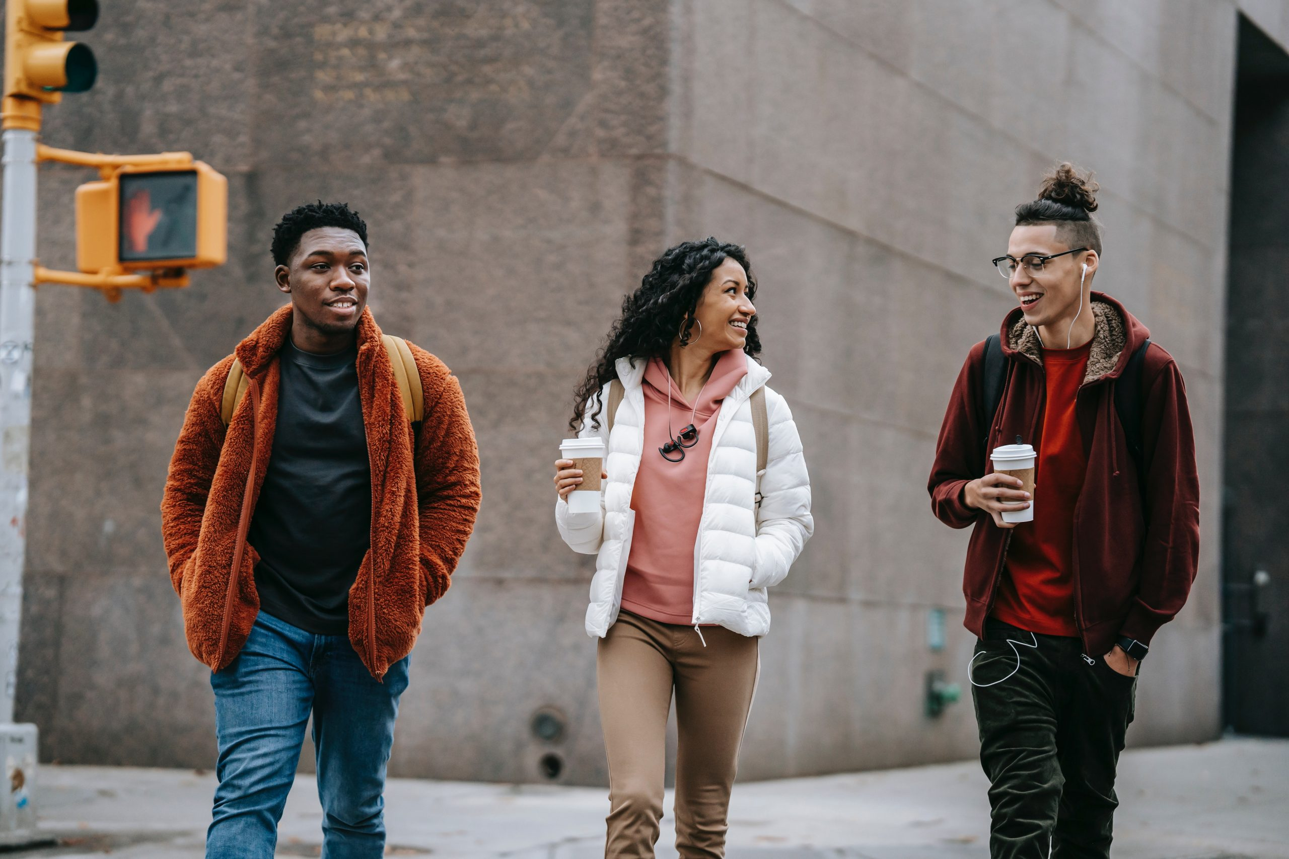 Photo of a white teen male holding a coffee cup and walking with a Latina teen also with a coffee cup and an African American male teen. They are all smiling as they walk down the street conversing with each other which could represent how much better they feel since starting online anxiety treatment for teens with a Solution Focused Brief Therapist in Illinois.