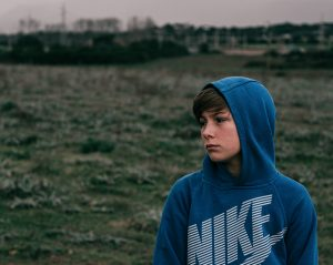Picture of teen boy wearing blue nike hoodie looking off into space. Learn how to avoid common pit falls in anxiety in kids and teens from anxiety therapist who can help. Or have your teen begin online anxiety counseling for teens in illinois or Chicago. Champaign 61820 | Huntley 60142 | Naperville 60440 | Hinsdale 60520