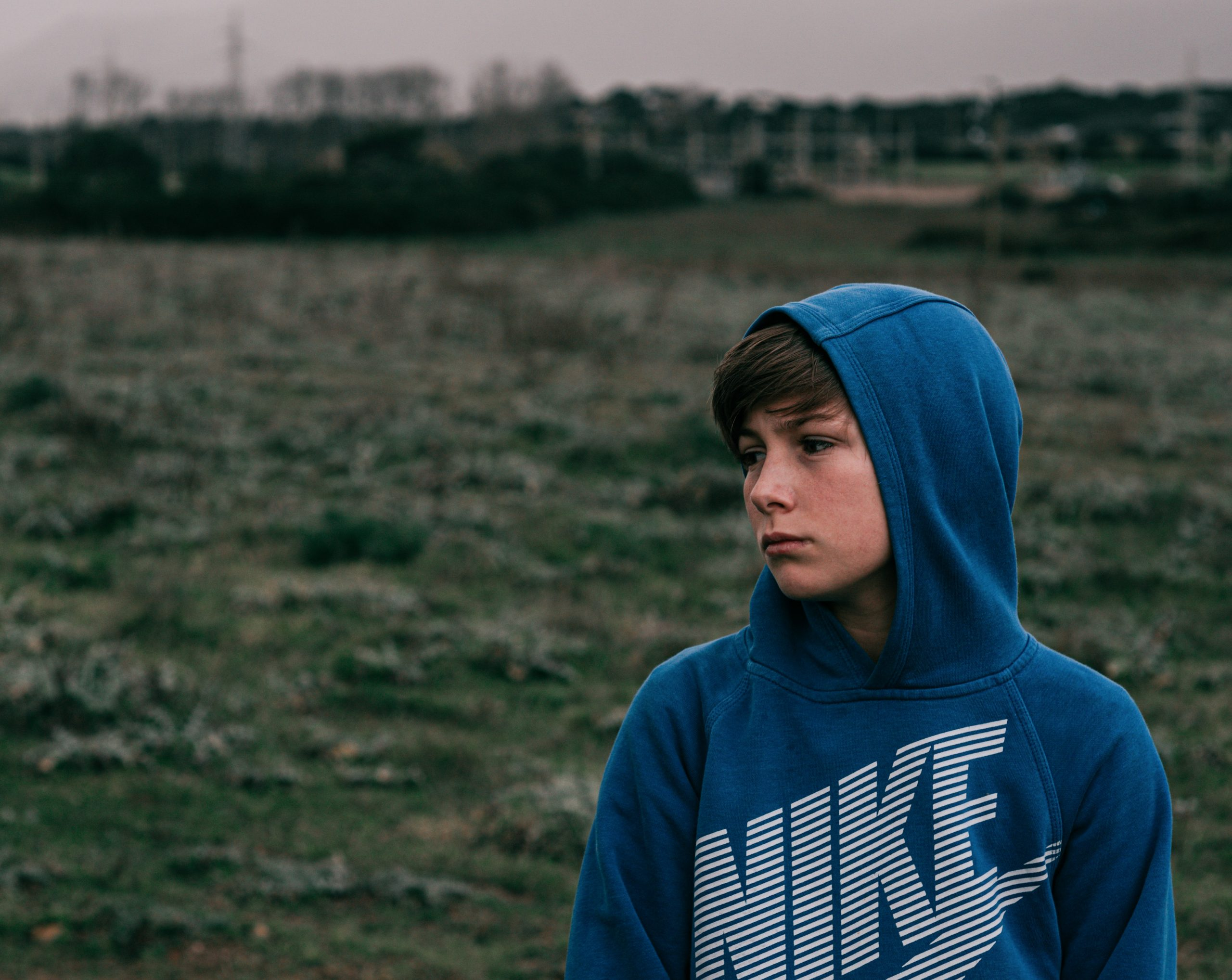 Photo of sad Caucasian male teen wearing blue NIKE hoodie and standing in a grassy field. Photo could represent how this teen feels before receiving online anxiety treatment in Illinois.