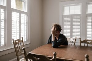 Male teen sitting at table with head in hands looking out window. Your teen may need online anxiety treatment, but doesn't know how to ask for help. Try getting them started in counseling for anxious kids in Illinois today for relief and guidance.