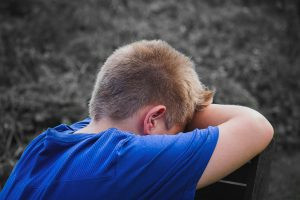 Caucasian boy wearing a blue t-shirt with his face resting downward on his right arm. Dealing with anxiety is stressful, get help with an online anxiety therapist in Illinois. Begin anxiety treatment in Illinois for worried kids with anxiety and phobias soon!