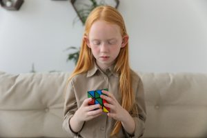 Young redheaded girl looking down at rubix cube. If your child is struggling with anxiety and phobias, I am here to help. Begin online therapy for kids in Illinois today. Don't continue to let anxiety in kids in Chicago, and Illinois hold them back. Call now!