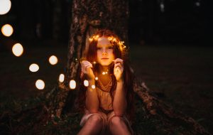 Young girl with lights around head and background sitting in dark. Beginning online therapy for kids in Illinois can help them overcome anxiety and phobias. Consider working with a skilled online therapist in Illinois who offers online therapy today! Get your worried kids the help they deserve from a solution focused therapy perspective.