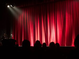 Red stage curtain with spotlight shining on it. A child's social anxiety and fear of performing in front of others can be helped with online anxiety treatment. Begin working with a skilled solution focused therapist who understands today. Begin counseling for anxious kids in Illinois or Chicago, IL soon!