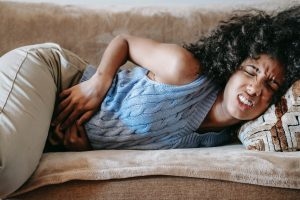 African american teen on couch hold stomach in pain. A symptom of anxiety can include somatic issues. Get help with anxiety treatment soon. Counseling for anxious teens in Illinois has been shown to reduce the psychological and physical distress of anxiety. Call now!