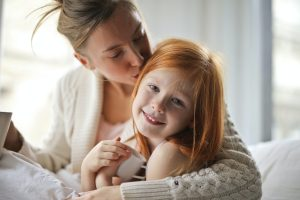 Mother holding red headed child and kissing head. When your child experiences anxiety, life is challenging. Begin to help them overcome anxiety symptoms with anxiety treatment today. Begin counseling for anxious kids in Illinois, with Helena Madsen for support.