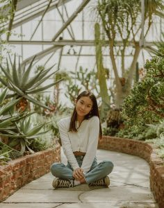 Asian teen sitting on ground in green house. After receiving online therapy for teen anxiety in Illinois, your teen can also feel the relief they have been seeking. Get started with anxiety treatment in counseling for anxious kids in Illinois soon!