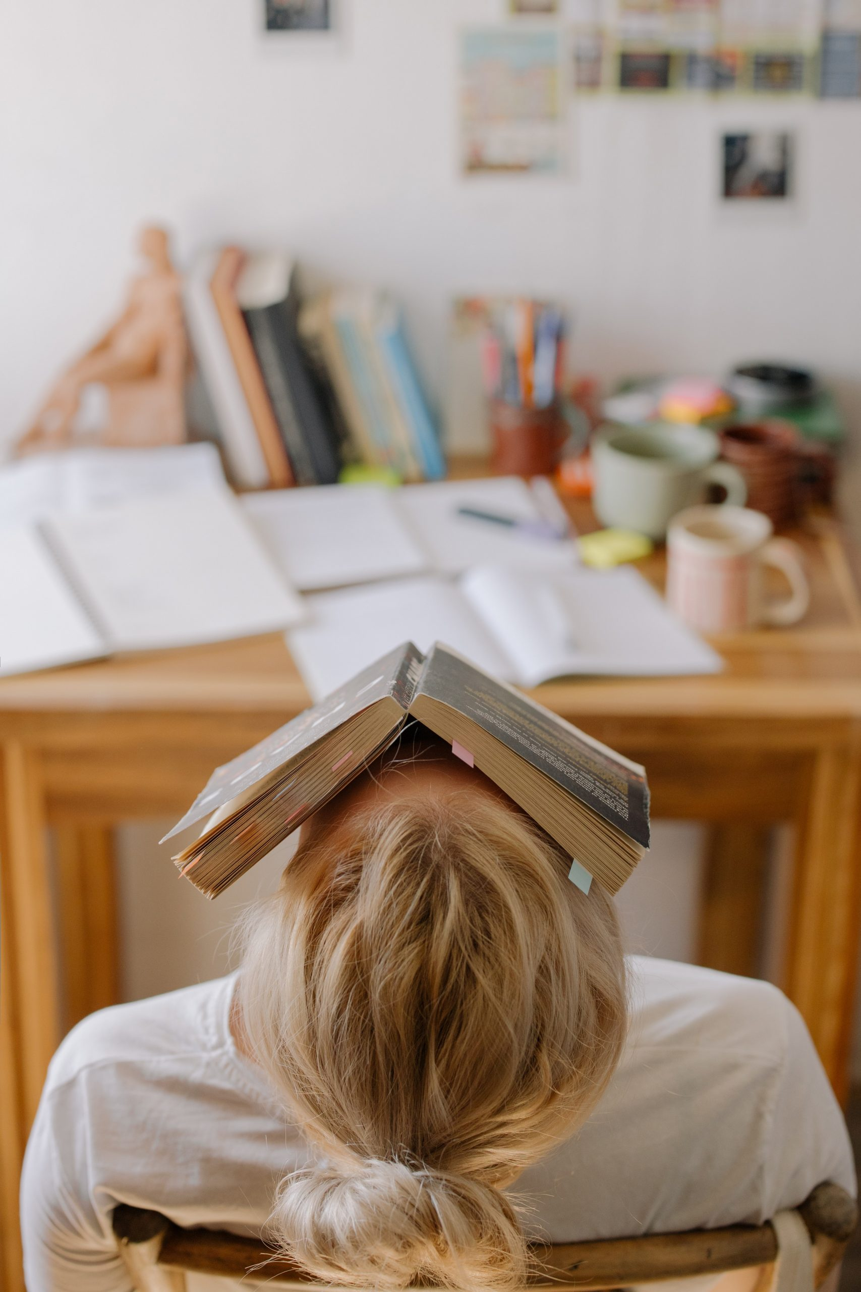 Photo of Caucasian teen girl with head tilted back and book on face as she sits in front of her desk. Photo represents her fatigue and lack of motivation when it comes to studying for her final exams; in which case she could benefit from online anxiety treatment for teens in Illinois.