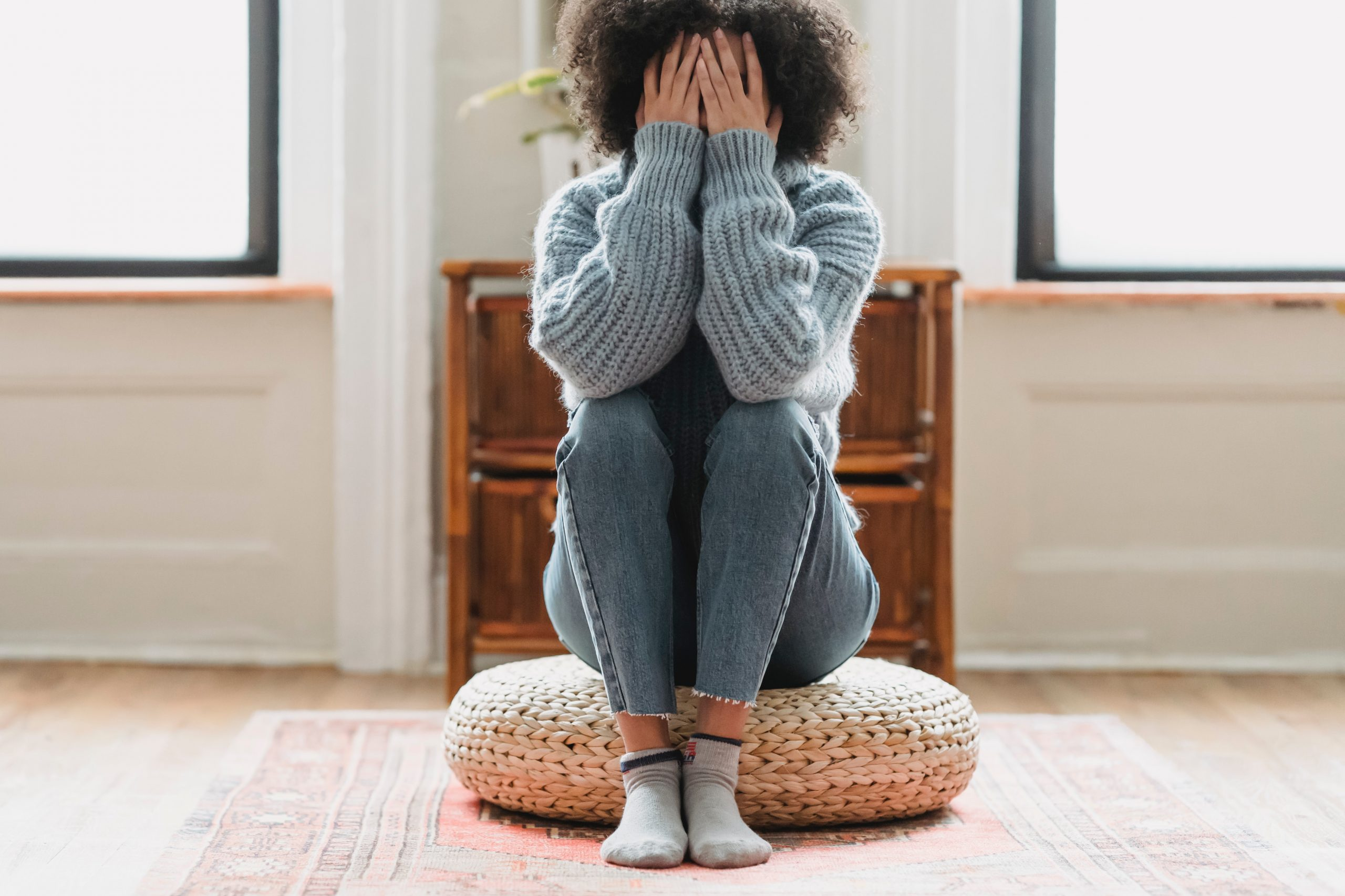 Photo of teenager sitting on the floor on a cushion with her hands covering her face. Photo could represent feeling of loss and grief over all she has missed during the Covid pandemic and her need for online anxiety therapy for teens in Illinois.