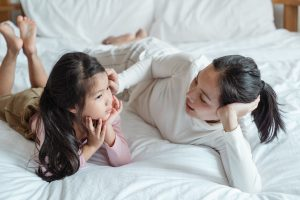 Mom laying on white bed with young daughter. If you're noticing anxiety in kids in Chicago, Il is overtaking your child, gets support from an anxiety therapist for dealing with anxiety. Call now and begin anxiety treatment in Illinois soon!
