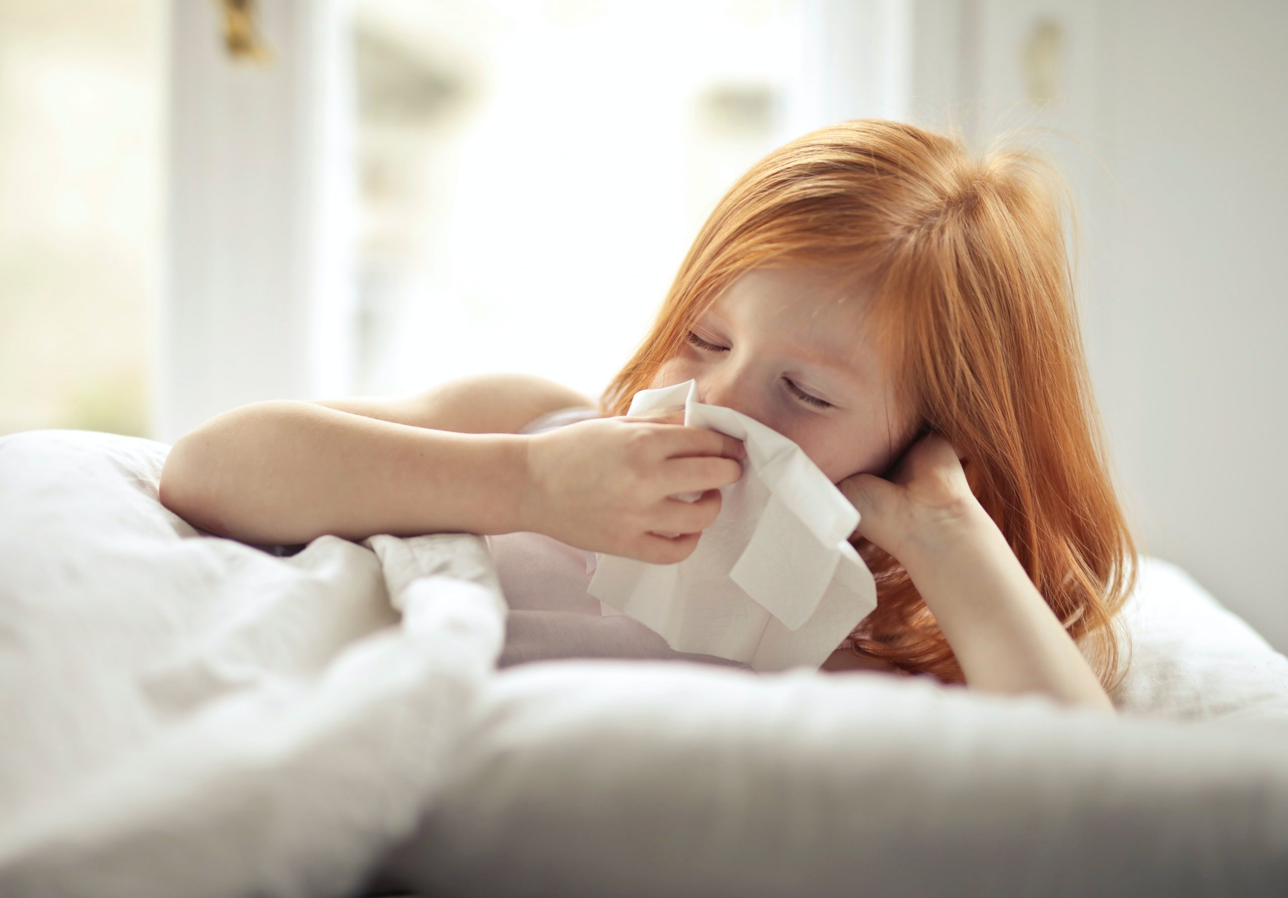 Photo of red headed Caucasian girl lying in bed sick and blowing her nose with a tissue. Photo could represent sickness anxiety and the need for online anxiety treatment in Illinois.
